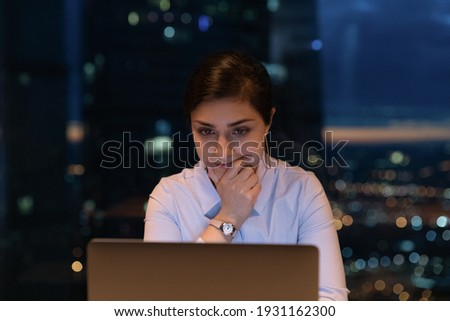 Close up thoughtful Indian businesswoman using laptop at late hours, finishing, working on project at night, touching chin, looking at computer screen, pondering, solving problem, deadline concept Foto stock ©