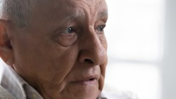 Close up thoughtful upset elderly man feeling lonely and depressed, looking to aside, lost in thoughts, mature widower thinking about past, nostalgia and melancholy, mental disorder, dementia