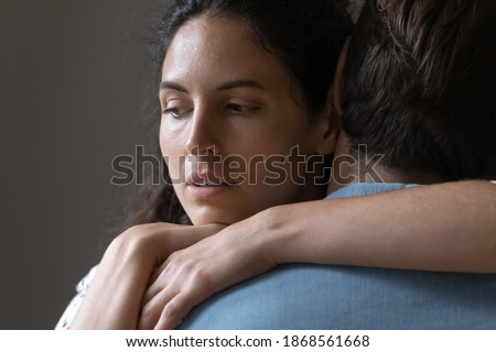 Close up thoughtful young woman hugging man, looking in distance, thinking about marriage problems, suspicious doubting wife embracing husband, pondering cheating in relationship, break up Stock photo ©