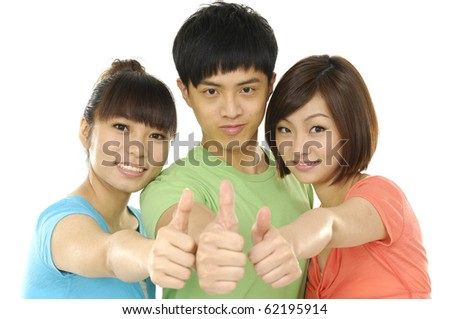 Close up three young teenagers laughing and giving the thumbs-up sign.