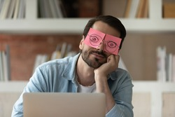 Close up tired businessman with stickers on face sleeping, drawn eyes on adhesive papers, sitting at work desk in office, unproductive lazy young male dozing, working on difficult project, fatigue