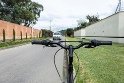 Close up to a black mountain bicycle handle bar with grips near to a green garden and blurred white van transit over asphalt way.