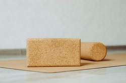 Close up to a cork block and blurred cork roller for MFR in background on a cork yoga mat