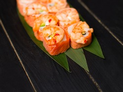 Close up to Delicious Japanese seafood sushi roll with salmon tataki and roasted black tiger shrimps on top served on bamboo leaves on black wooden background