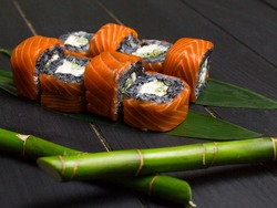 Close up to Japanese black rice sushi roll with raw salmon on top served bamboo leaves with bamboo sticks out of focus on foreground. Cucumber and cream cheese wrapped in rice. inside out roll
