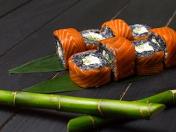 Close up to Japanese black rice sushi roll with raw salmon on top served on green bamboo leaves with bamboo sticks out of focus on foreground. Cucumber and cream cheese wrapped in rice