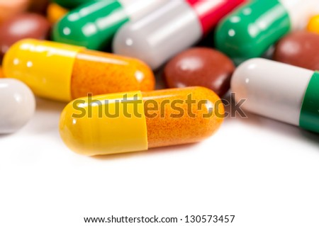 Close up to pills. Selective focus on the yellow pill - stock photo