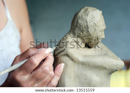 Close up to Sculptor's hand and her sculpture while she is working on it