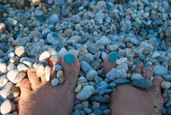 Close up toes with bright pedicure and stones on the beach