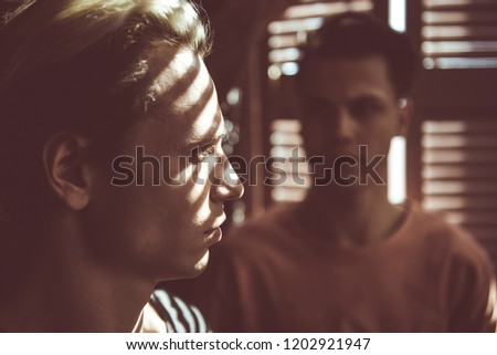 Close up toned portrait of attractive guy with shadow from jalousie on his face looking away with serious expression. Dark-haired man on blurred background