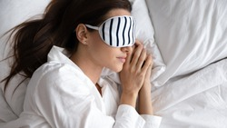 Close up top view brown-haired woman in white sleepwear striped eye mask lying at soft pillow on one bed side, accessory to ease sleeping, comfort rest, orthopedic mattress, enjoy sweet dreams concept