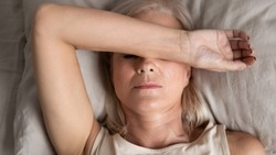 Close up top view middle-aged woman lying down in bed on pillow put hand on face, concept of female having insomnia sleeping disorder or migraine pain, melancholic mood, personal life troubles concept
