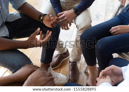 Close up top view multiracial people seated in circle talking analysing share mental problems during psychological rehab session, anonymous alcoholics association addiction treatment community concept