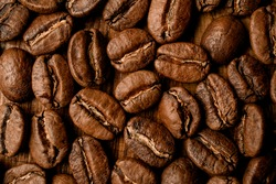 close-up top view of beautiful aromatic dark roasted coffee beans. Brown seed, texture background, wallpaper