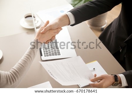 Close up top view of business handshake, male and female hands shaking over office desk after signing contract, holding signed statement, sealing deal as good result of successful negotiations  #670178641