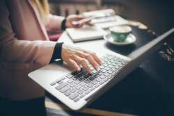 Close-up top view of Caucasian woman's hands Casually dressed student, blogger, writer man working on a laptop holding a phone in his hand, inside the cafe a wooden table and a cup of coffee.