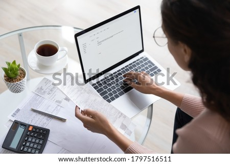 Close up top view of concentrated woman work on laptop manage family expenditures expenses using gadget, focused housewife busy calculating finances, plan budget on computer, pay bills or taxes online