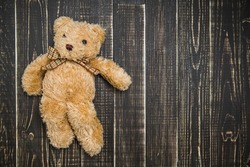 Close up top view of cute soft brown teddy bear laying on wooden shabby background. Horizontal color photography.