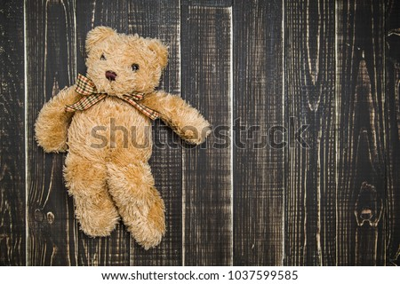 Close up top view of cute soft brown teddy bear laying on wooden shabby background. Horizontal color photography. #1037599585