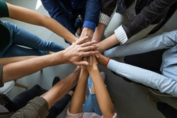 Close up top view of diverse businesspeople stack hands motivated for shared business success at briefing, multiracial colleagues engaged in teambuilding activity show unity support at office meeting