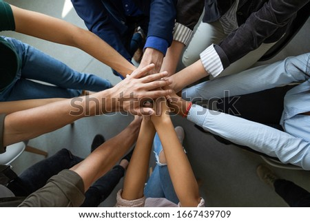 Close up top view of diverse businesspeople stack hands motivated for shared business success at briefing, multiracial colleagues engaged in teambuilding activity show unity support at office meeting Stock photo ©