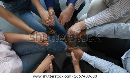 Close up top view of diverse multiracial businesspeople sit in circle hold hands showing support and unity, multiethnic colleagues employees engaged in teambuilding activity or training at briefing