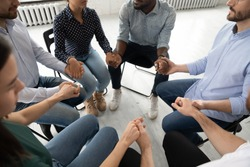 Close up top view of diverse young people sit in circle holding hands participate in group therapy, multiracial patients give psychological help or support engaged in counseling session together