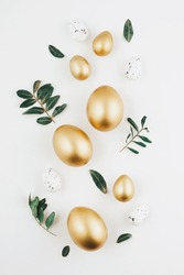 Close-up top view of golden Easter eggs on white background, Happy Easter minimal concept