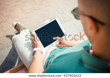 Close-up top view of man holding digital tablet while sitting outdoors. business person browsing internet or connecting to wireless via touchscreen pad #437402623