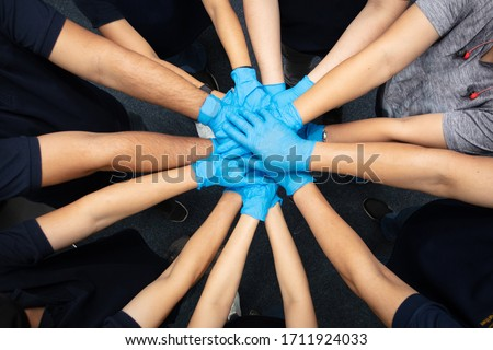 Close up top view of Volunteer  people putting their hands together. Stack of hands showing unity and teamwork to fighting corona virus (Covid-19)