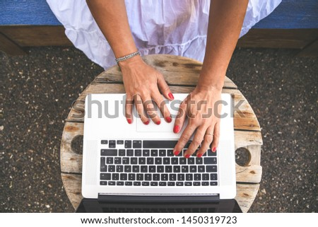 Close up top view of woman hands typing on a laptop keyboard. Girl working with computer online sitting outdoors in the home patio. New trends technology and communication concept in rural contest. stock photo