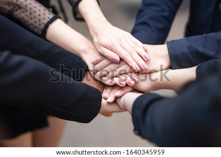close up top view of workers putting hands together piling on top of one another representing teamwork, community help and support within the small business or company within an office environment Stock foto ©