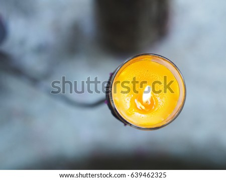 Close up top view of yellow candle in glass on metal stand #639462325