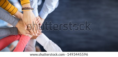 Photo of Close up top view of young business people putting their hands together. Stack of hands. Unity and teamwork concept.