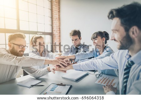 Close up top view of young business people putting their hands together. Stack of hands. Unity and teamwork concept. #696064318