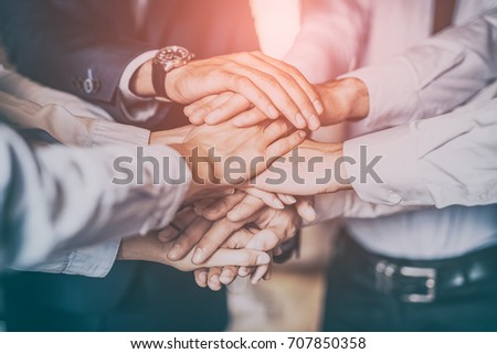 Close up top view of young business people putting their hands together. Stack of hands. Unity and teamwork concept. #707850358