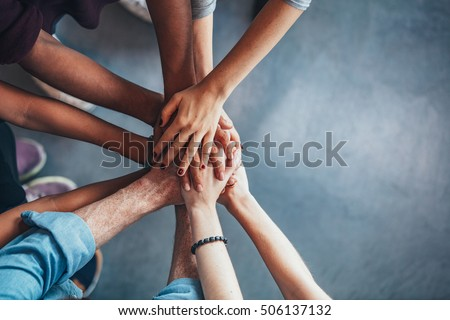 Photo of  Close up top view of young people putting their hands together. Friends with stack of hands showing unity and teamwork.