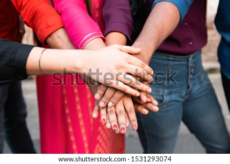 Close up top view of young people putting their hands together. Indian Friends with stack of hands showing unity and teamwork. #1531293074
