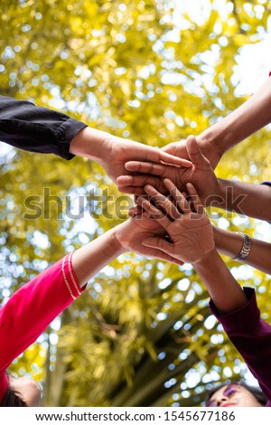 Close up top view of young people putting their hands together. Indian Friends with stack of hands showing unity and teamwork #1545677186
