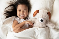 Close up top view toddler asian girl lying in bed with plush animal dog toy woke up looks at camera feels happy. Comfy mattress, dry diaper, soft pillow, fresh bedding, healthy enough sleeping concept