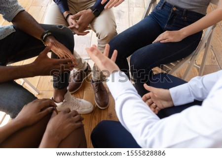 Close up top view unrecognizable diverse businesspeople talks seated on circle indoors take part in seminar team building training activity, rehab session addiction treatment community meeting concept