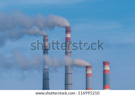 Close-up tops of smoking pipes of power plant on blue sky background, horizontal photo,
