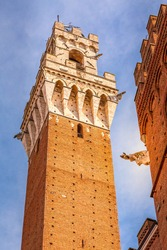 Close-up Torre del Mangia medieval tower, located in Piazza del Campo, iconic landmark of Siena, Italy