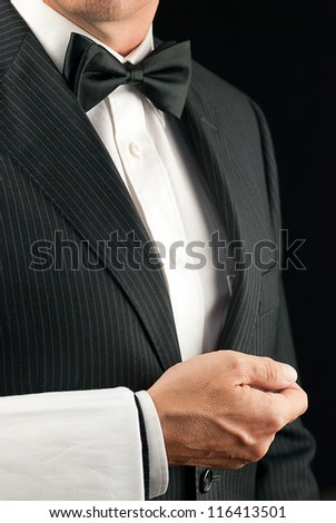 Close-up torso shot of a fine dining waiter in a bowtie and tux with a white pressed napkin over his arm. Side View.