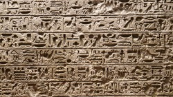 CLOSE UP: Traditional Egyptian lettering and symbols carved into a large slab of solid stone. Detailed view of beautiful hieroglyphs carved into a stone wall in a museum of ancient history in Rome.
