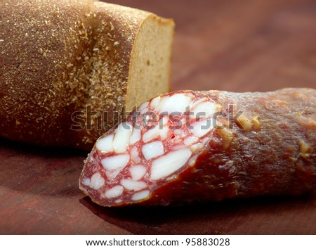 Close-up traditional  sausage salami on wooden board with loaf of homemade brown bread - stock photo