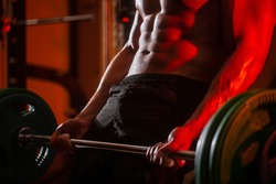 Close up training with barbell. Man lifting barbells working out in gym. Closeup deadlift barbells workout. Sporty man lifts barbell in gym. Workout the gym. Athletic man with six pack, perfect abs.