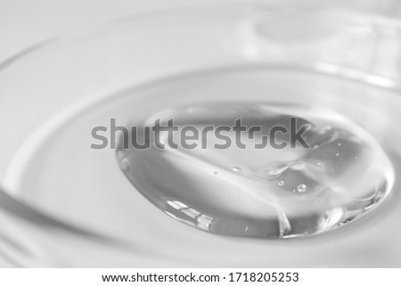 Close-up transparent aloe gel in glass petri dish smudge on white background. Concept laboratory tests and research, making cosmetic. Purity facial cleanser, peeling, shampoo or shower gel