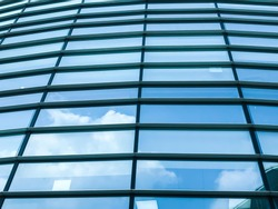Close up transparent glass window panes on corporate office building reflecting blue sky and cloud