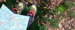Close-up traveler using local map. Top View of Hiking Boot on the trail. Legs In Jeans And sport trekking shoes on rocky stones of Mountains. Local travel
